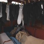 Leander schläft auf der Bank im Salon, unter der Decke hängen Socken zum Trocknen