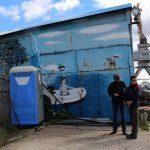 Peter und Leander stehen vor einem Dixie-Klo, daneben ein Wandbild mit einem Mann in einem Schlauchboot