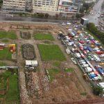 Ausgrabungsstätte, von oben fotografiert, daneben die Stände des Bauernmarktes
