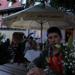 Leander am Restauranttisch hinter einem Blumengesteck hervorschauend
