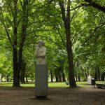 Helle Skulpturen auf grauen Sockeln unter Parkbäumen