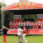 vor der Bühne, auf der die Gesangsgruppe auftritt, tanzt ein Paar auf dem Gras