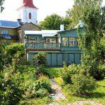 Garten mit Holzhaus im Hintergrund, dahinter der Turm der Kirche
