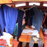 Peter am Salontisch auf RITH mit der Seekarte beschäftig, überall hängt Wäsche