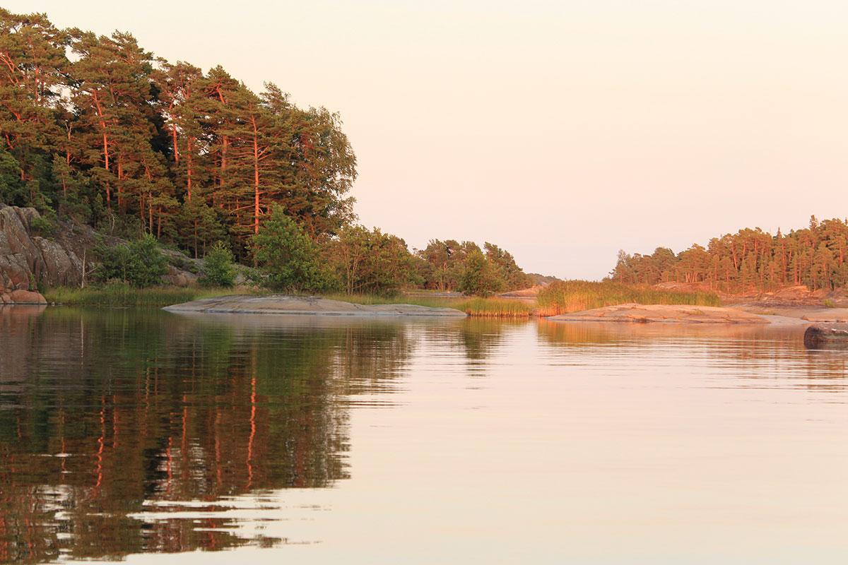 Zwei kleine Felsen, die aus dem Wasser schauen im Abendlicht, der eine graublau, der andere orangerot erscheinend