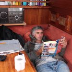 Peter liegt auf der Bank im Salon und liest