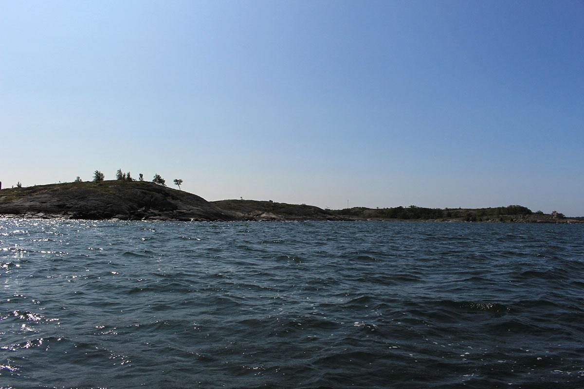 karge Felseninsel mit ein paar kleinen Bäumen im Gegenlicht