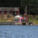 eine Hütte im schwedischen Stil, davor ein Badesteg, hinter dem ein riesiger aufblasbarer Flamingo schwimmt
