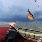 Annette am Steuer von Rith, von hinten zu sehen, weil sie sich gerade nach der blaugrauen Gewitterwolke mit dem ausgefransten Böenkragen am Himmel hinter ihr umschaut
