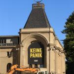 """Teilansicht des Berliner Ensembles mit dem Plakat """"Keine Panik"""""""