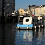 auf der Spree: eine Art Floß, auf dem ein Wohnwagen steht. Hinter dem Wohnwagen, erhöht, ein Mann, der das Gefährt steuert