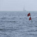 Im Vordergrund ein Stange mit zwei roten Fahnen, mit denen die Fischer ihre Netze markieren, dahinter im Dunst eine segelnde Yacht