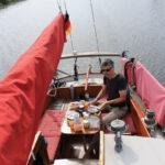 Peter sitzt am Tisch in der Plicht, frühstückt und steuert Rith den Ryck hinauf nach Greifswald