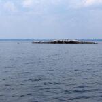 Ein dickes Leitungsrohr erhebt sich aus dem Wasser wie der Rücken von Nessie aus dem Loch Ness