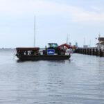 eine kleine Fähre transportiert einen Traktor von der Öhe aufs Festland