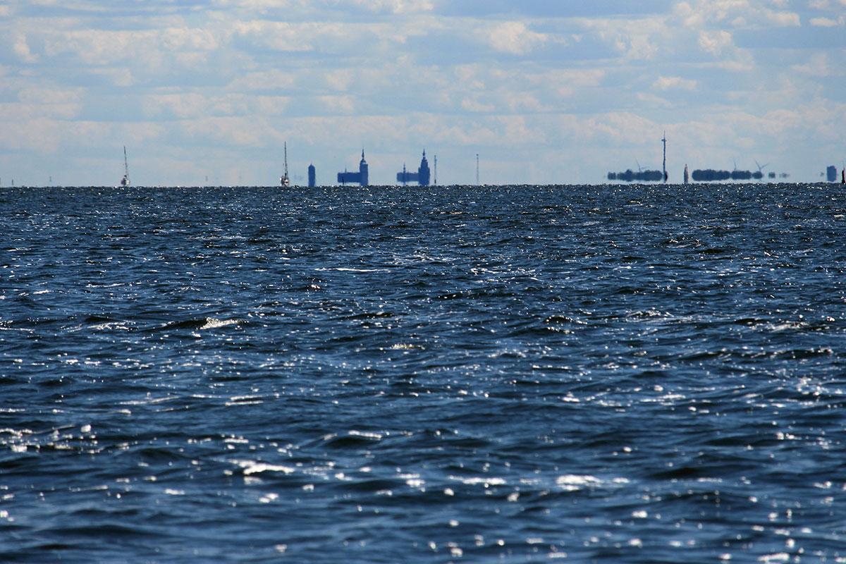 eine große Wasserfläche, am Horizont die Kirchen von Stralsund